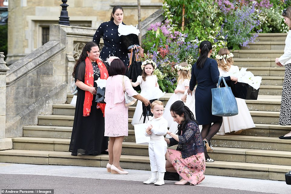 Bridesmaids and page boys wait on the steps of St George's Chapel before going in for the wedding