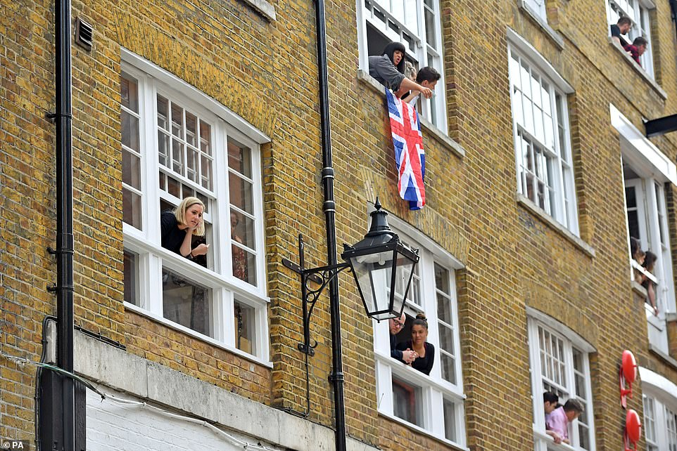 Excited residents and workers hung out the windows to catch a glimpse of Her Majesty