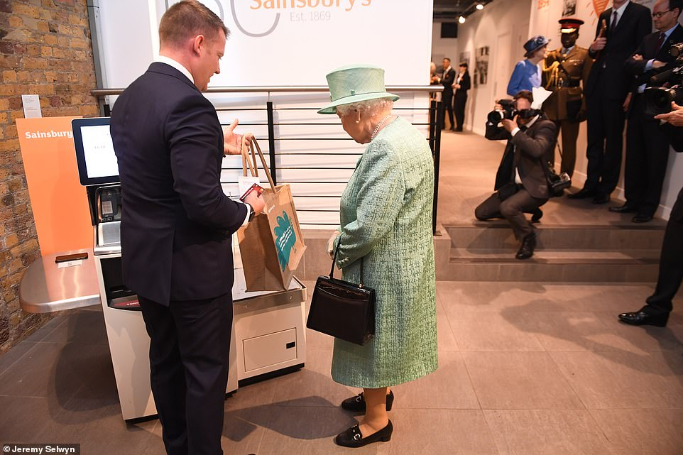 The Queen was talked through the technology of a self-service checkout during her visit today, pictured. A member of staff also showed the Queen an example of the retailer's reusable bags for life, which were introduced to reduce plastic waste