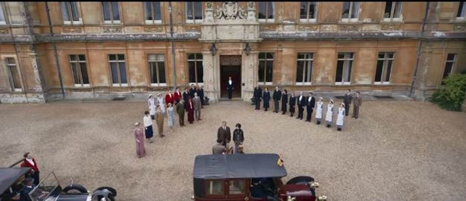 Making their entrance: A wide shot shows the royal motorcade pulling up to Downton Abbey where the household waits