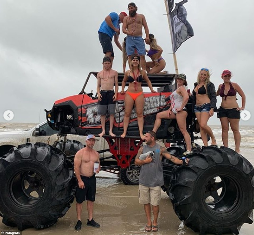 A group standing on the wheels, side-skirts and roof of a massive monster truck close to the shoreline at Crystal Beach