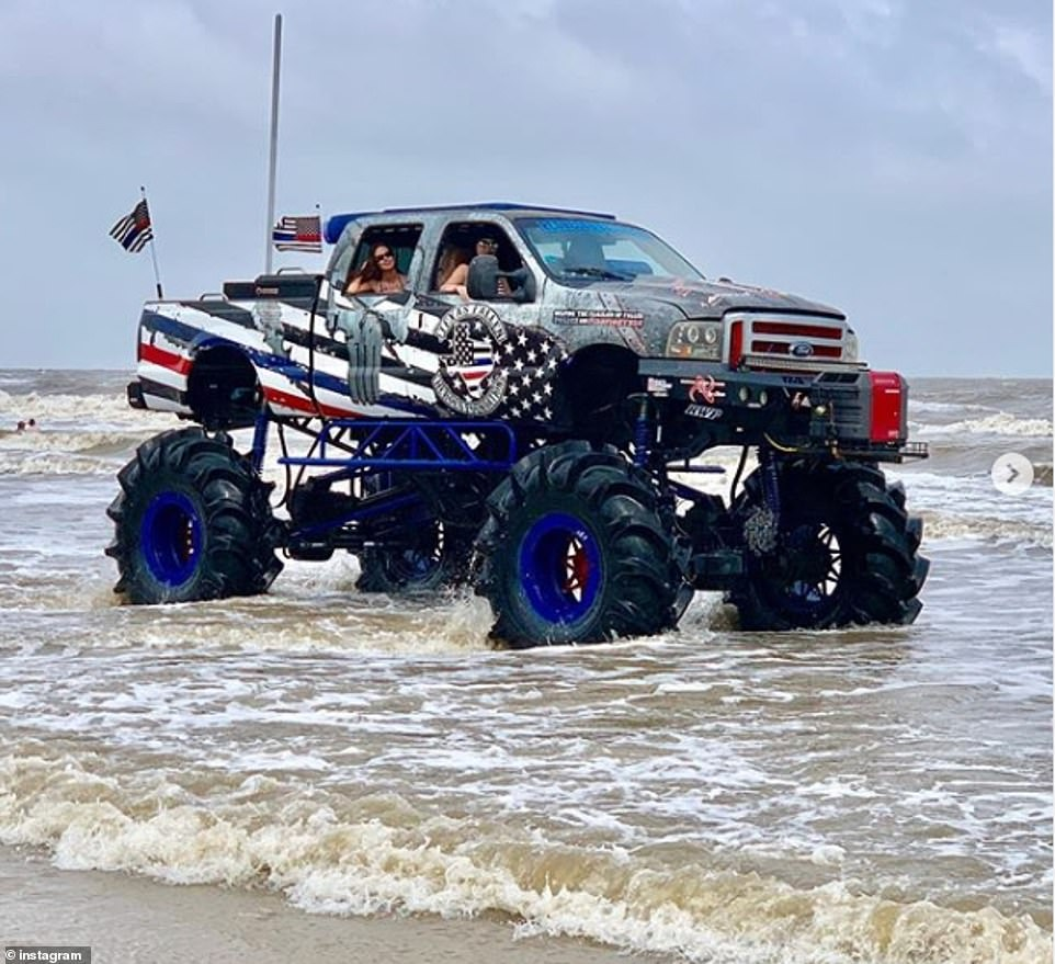 A colossal monster truck covered in the stars and stripes with a Texas emblem rolls through the waves on the beach