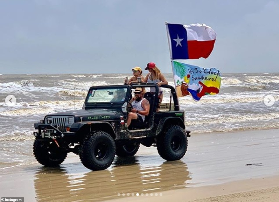 A group ride across the beach, two men are seated in the front with two women standing in the back of the topless 4x4