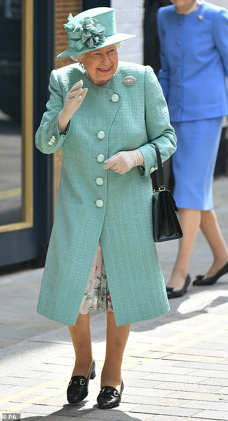 The Queen looked elegant in a mint green coat and matching hat for the outing in central London this morning