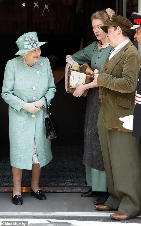 The Queen has taken a trip back in time with a visit to a replica of the first Sainsbury's supermarket. Pictured, the monarch speaks to actors in period costume