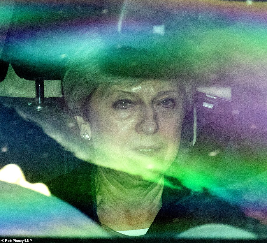 A bleary-eyed Theresa May leaves Parliament in the back of her car after a brutal day in Westminster yesterday