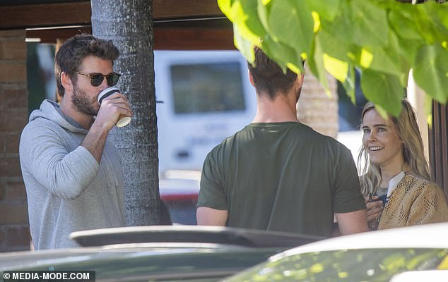 The future's bright!Liam, 29, sported a grey hooded top and navy shorts, and concealed his gaze behind designer sunglasses