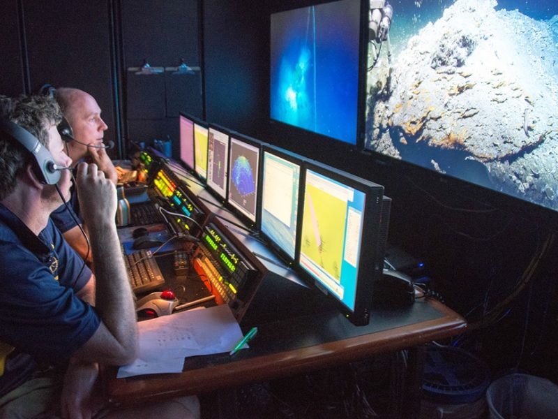 Scott Sofolofsky (background) and GISR PI Chip Breier (foreground) work in the ROV control room on the E/V Nautilus