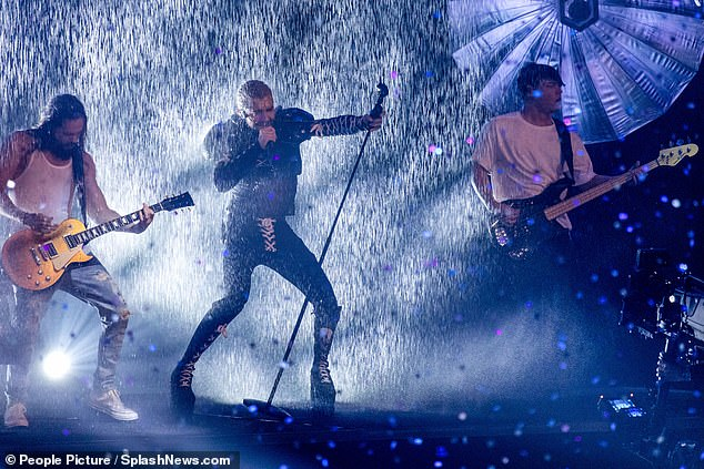 Proud partner: Heidi's beauTom performed as a dramatic rain shower poured down