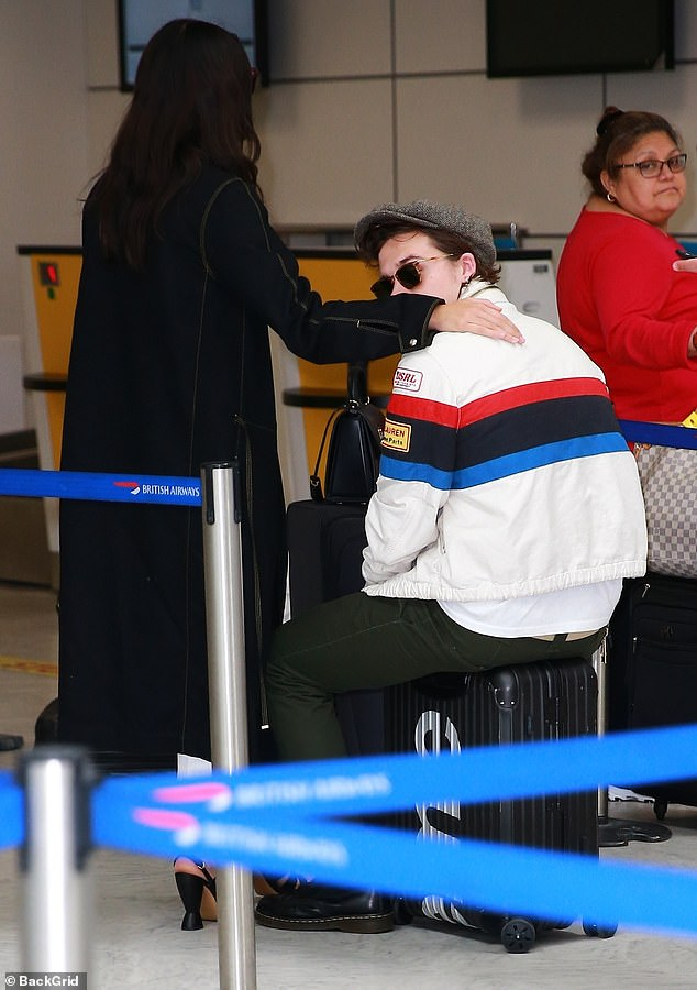 Need a lie down? Brooklyn rested on his Supreme suitcase as Hana threw her arm around him