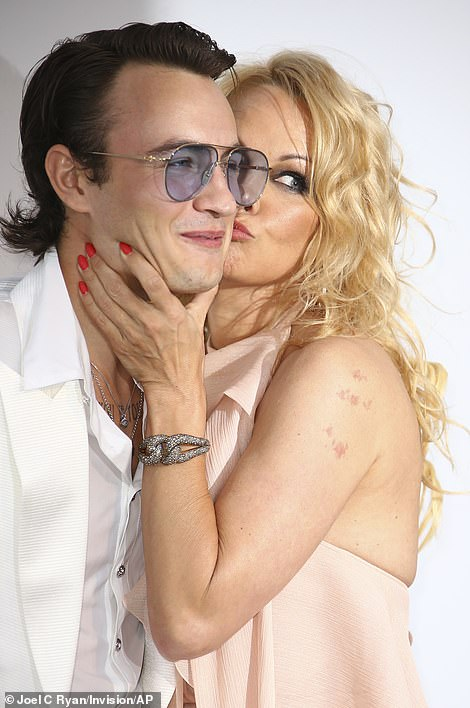 Doting mum: Pamela was joined by her son Brandon Lee, 22 - who she shares with ex Tommy Lee - and she couldn't resist smothering him with kisses on the cheek