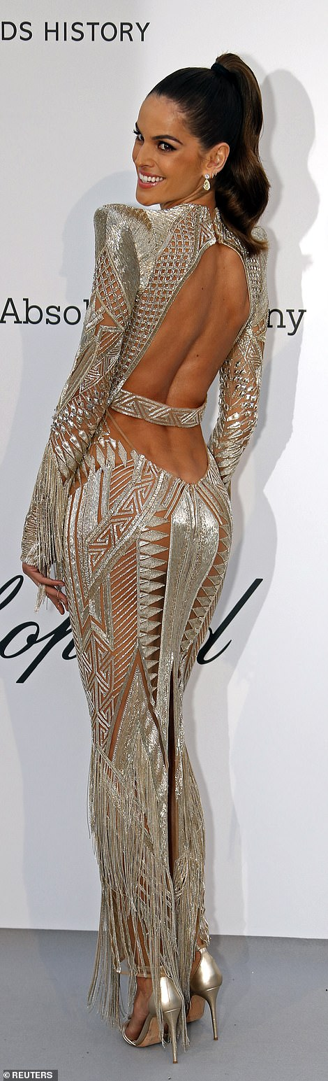 Silver lining: Izabel Goulart also put emphasis on her fantastic figure in a silver metallic cut-out number which plunged down the middle to show off her cleavage