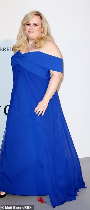 Looking good: Rebel Wilson stunned in a midnight blue gown which fell off the shoulders. She added to the glamorous look with a sensational blowdry