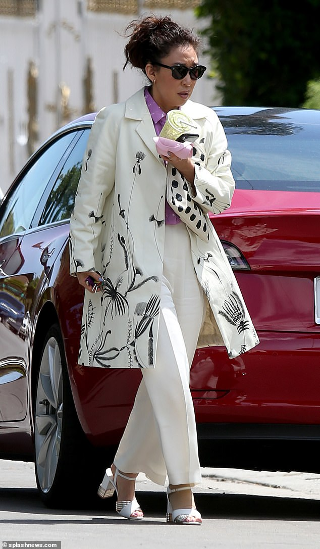 Looking chic: Sandra, 47, looked gorgeous for her fun afternoon, pairring white wide-legged trousers with a long-line cream jacket dotted with a pretty black floral print