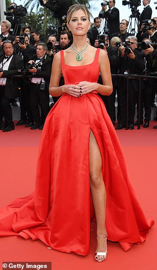 Catching the eye: Brazilian blogger Lala Rudge was a vision in red as she slipped into a square-necked belted number, while narrowly avoiding a wardrobe malfunction with its thigh-high slash