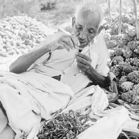 After a long day of work harvesting durra, a man sits and relaxes while chewing khat in Ethiopia. Georg Gerster/Photo Researchers, Inc.