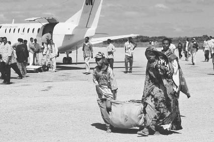 A family in Somalia carries a bag of fresh khat from a cargo plane at the airport. In Somalia chewing khat after a meal is common. In the United States and Canada, it is illegal. Liba Taylor/Corbis.