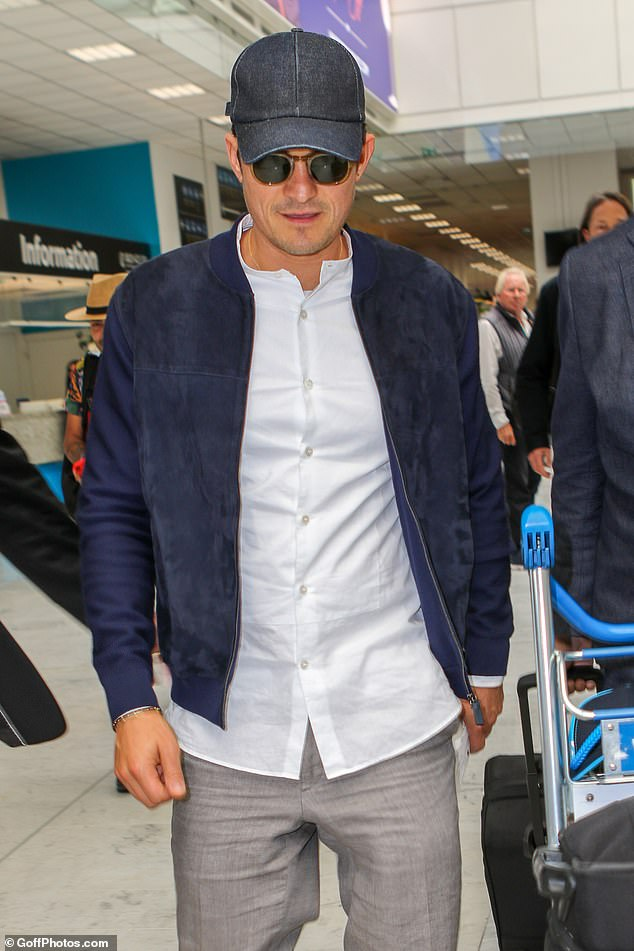 Stylish: Orlando added a navy bomber jacket to his look as well as a denim baseball cap, while shielding his eyes from the rays with a pair of wayfarer shades