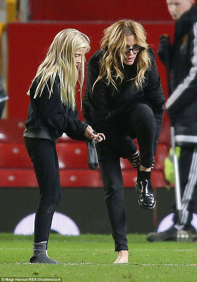 Julia Roberts is seen changing her boots on the soccer pitch after a match with daughter Hazel in Manchester, UK on November 27, 2016. Roberts and her daughter paid a visit to the Kennedy family this week