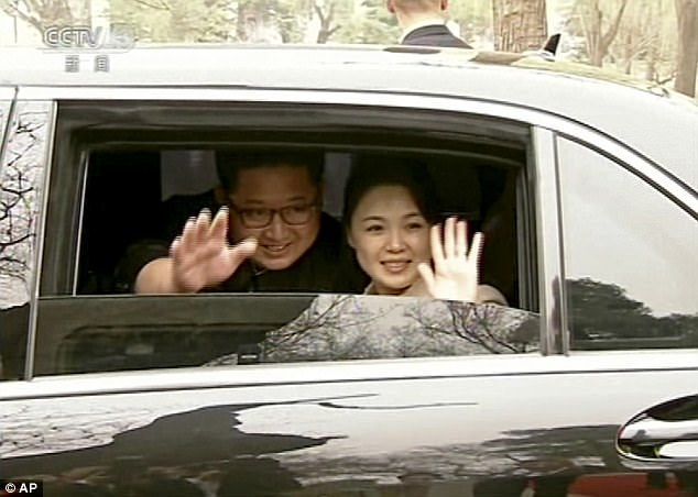 Kim Jong Un, left, and his wife Ri Sol Ju wave from a car as they bid farewell to President Xi and his wife, Ri Sol Ju