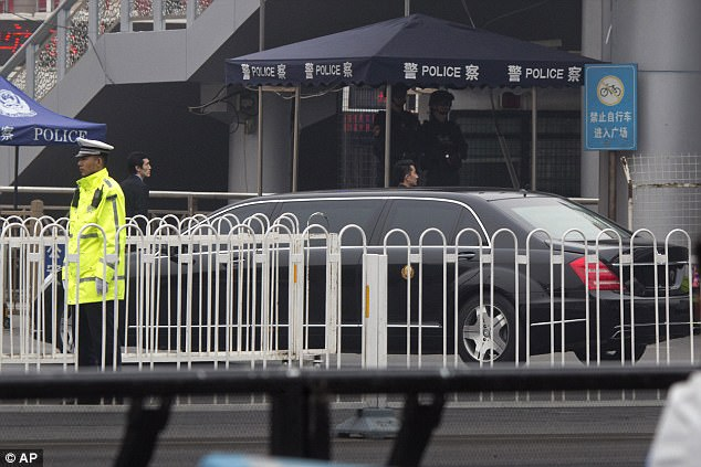 A limousine without car plates and bearing a gold color emblem on its side arrives amid heavy security at the train station in Beijing