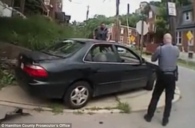 Fatal shooting: A newly-released video, captured on UC Officer David Lindenschmidt's bodycam, appears to show Lindenschmidt backing up his colleague  Ray Tensing's alleged lies over the shooting of driver Samuel DuBose. Above, this still from the video shows Tensing and Officer Phillip Kidd approaching DuBose's car