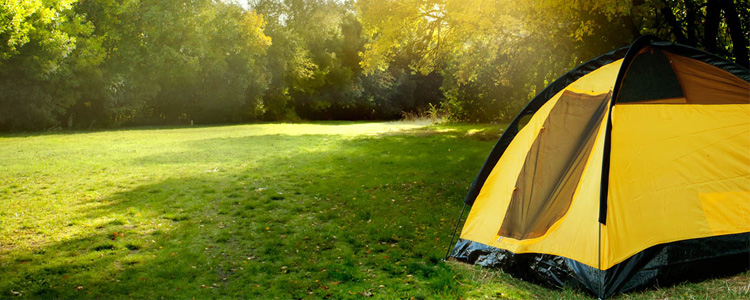 Tent on a sunny campground. Camping on a budget is possible.