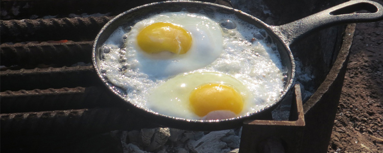 Eggs in a pan cooking on the campfire. Camping on a budget is easy.