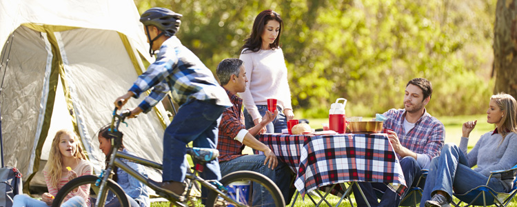 Family eating dinner at campground. Tips for camping on the cheap.