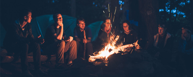 Friends gathered around a campfire. Friends help make camping affordable.