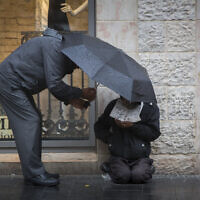 Illustrative. A man gives money to a homeless person, as he holds an umbrella to protect them both from the rain on Jaffa Street, Jerusalem, on November 3, 2014. (Yonatan Sindel/Flash90/File)