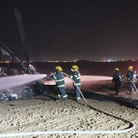 Firefighters work to extinguish a blaze on a helicopter that made an emergency landing in a field outside of Rahat in the Negev desert on November 26, 2019. (Fire and Rescue Services)