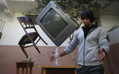 In this Nov. 20, 2019, photo, Mohammed al-Shenbari demonstrates balancing of objects using what he calls a mix of mind and body, in the yard of his home in Beit Hanoun, northern Gaza Strip. (AP Photo/Hatem Moussa)