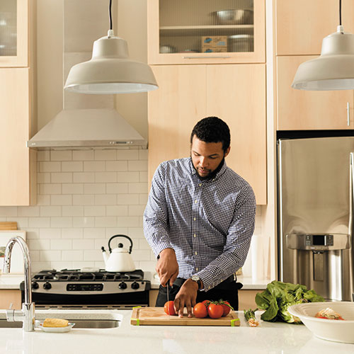 african american man cutting tomatoes in kitchen