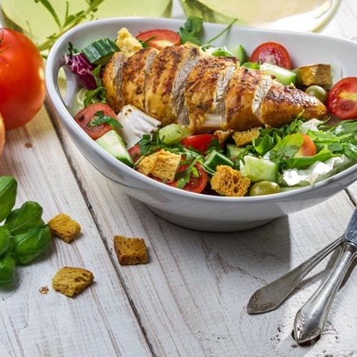 sliced chicken breast in salad bowl with vegetables