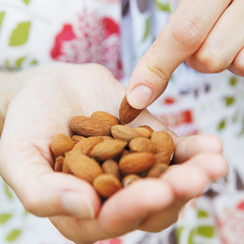 woman holding almonds in hand