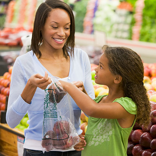 african american mom daughter shopping for fruit