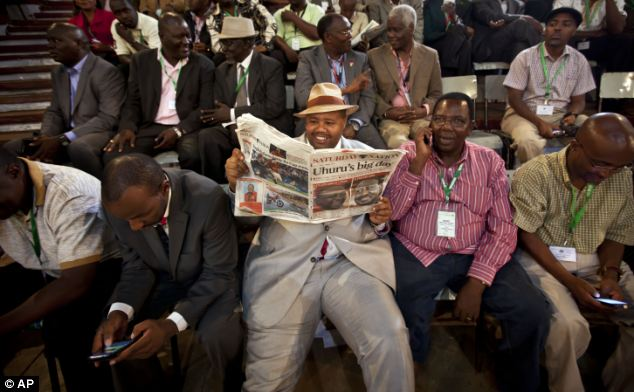 Guests read a newspaper at the ceremony held at the National Election Center where final election results were announced