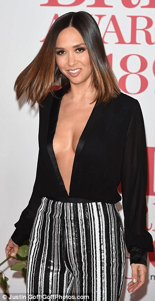 Racy lady: Myleene flaunted her gym-honed figure in the daringly low-cut bodysuit which was neatly tucked into a pair of striped seventies inspired trousers
