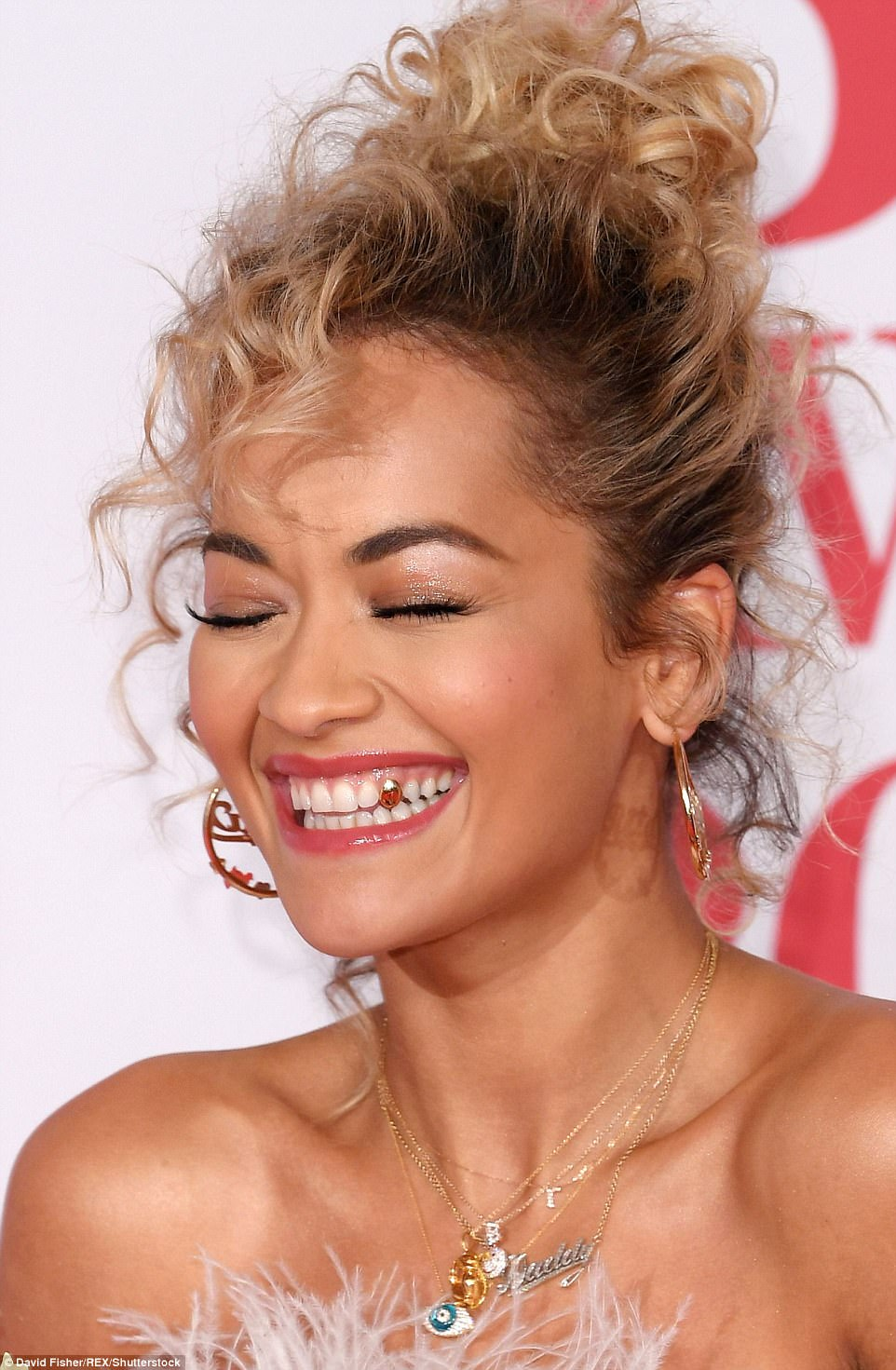 Going for gold: Rita showed off her gold tooth as she giggled on the red carpet