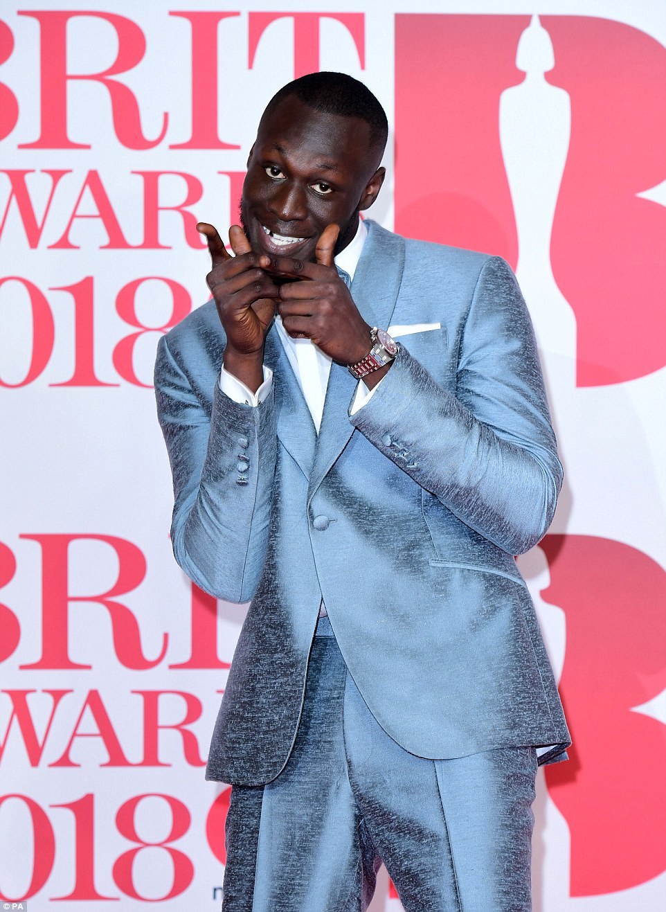 Looking good: While his girlfriend Maya posed elsewhere on the red carpet, Stormzy struck a number of fun poses in his eye-catching blue suit from Savile Row tailor, Richard James