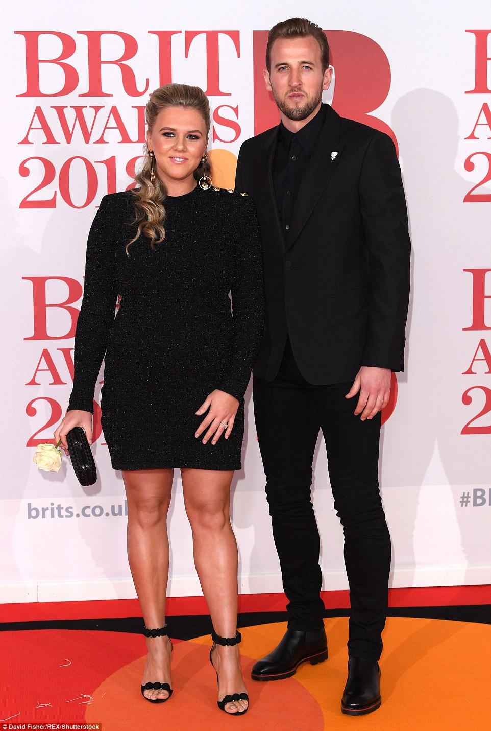 Footballer Harry Kane cosied up to pregnant fiancée Katie Goodland as she cradled her blossoming bump on the BRITs red carpet