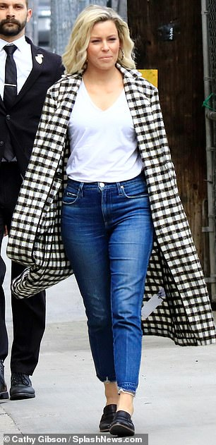 Statement coat: Elizabeth completed her ensemble with a plain white T-shirt and a pair of stylish black leather loafers