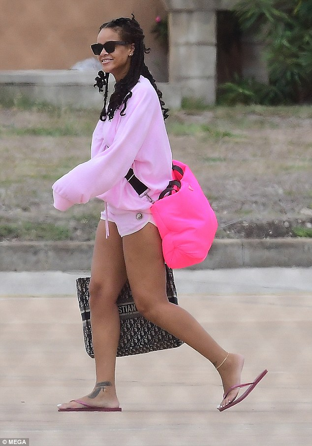 Electric: Rihanna showed off her eye for style as she rocked a bright pink ensemble at the airport in Barbados on Sunday morning