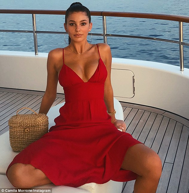 Leo's new flame: The pretty brunette posed in a red sleeveless dress with plunging neckline on board a yacht with legs akimbo as she continues her Mediterranean vacation