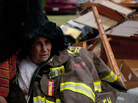 A firefighter (left) covers the survivor of a tornado that destroyed her mobile home east of Ben Wheeler, Texas, on Tuesday. She was shaken and had some minor bruises but otherwise escaped without serious injuries.