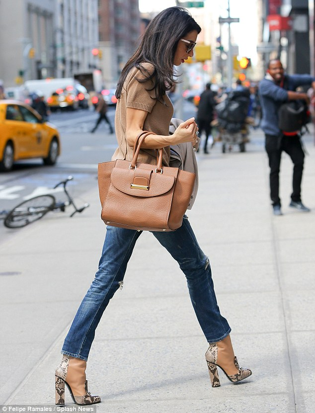 Neutrals: The wife of George Clooney also wore a tan knit and beige leather jacket while carrying a brown tote