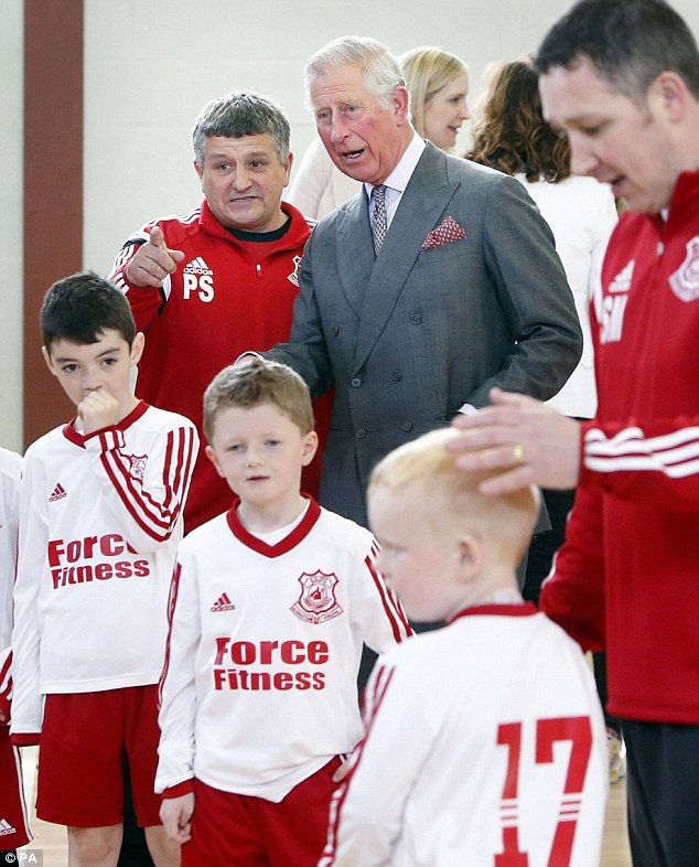 Advice: Charles listens in as young footballers at the centre are put through their paces by their coach