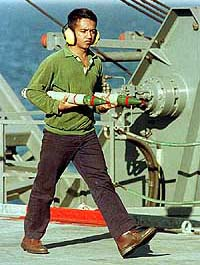 A flight attendant carries two missiles on the deck
