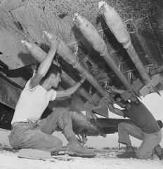5-inch rockets being loaded onto a Marine Corsair